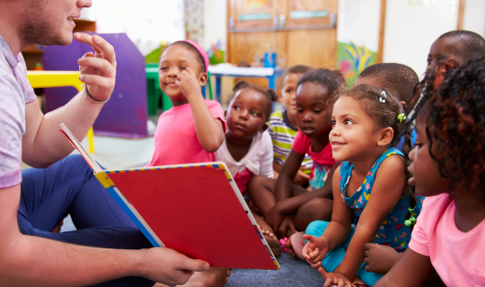 Group of children looking at teacher holding a picture book