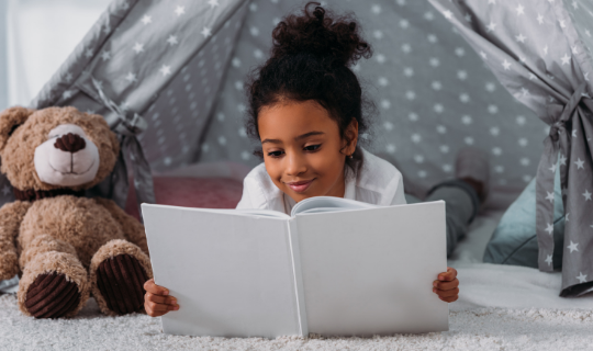Child holding a picture book in a blanket fort with pillows and a teddy bear