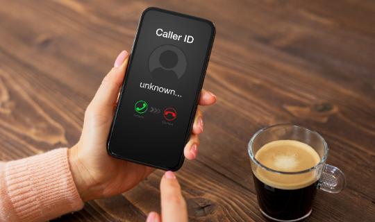 Smartphone with unknown caller on screen, understanding robocalls