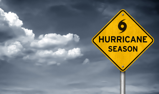 """Grey clouds behind a yellow sign with a hurricane symbol and the words """"hurricane season"""""""