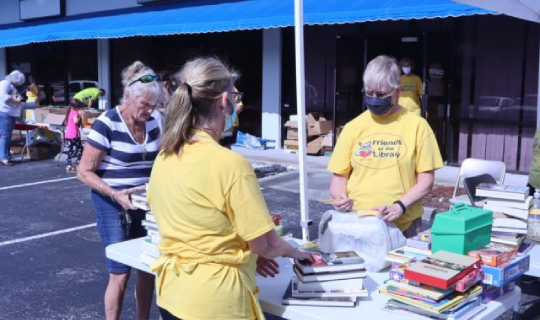 FOCCLS President Sandy Price and Vice President Janet add up a sale at a sidewalk sale