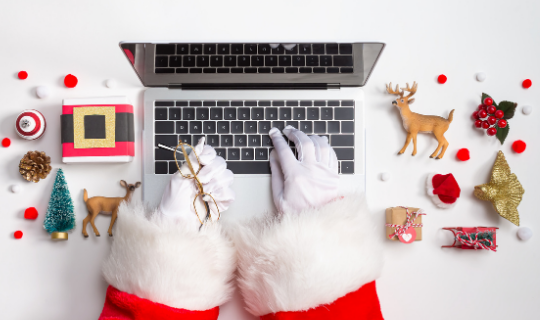 Santa typing on laptop with Christmas decorations