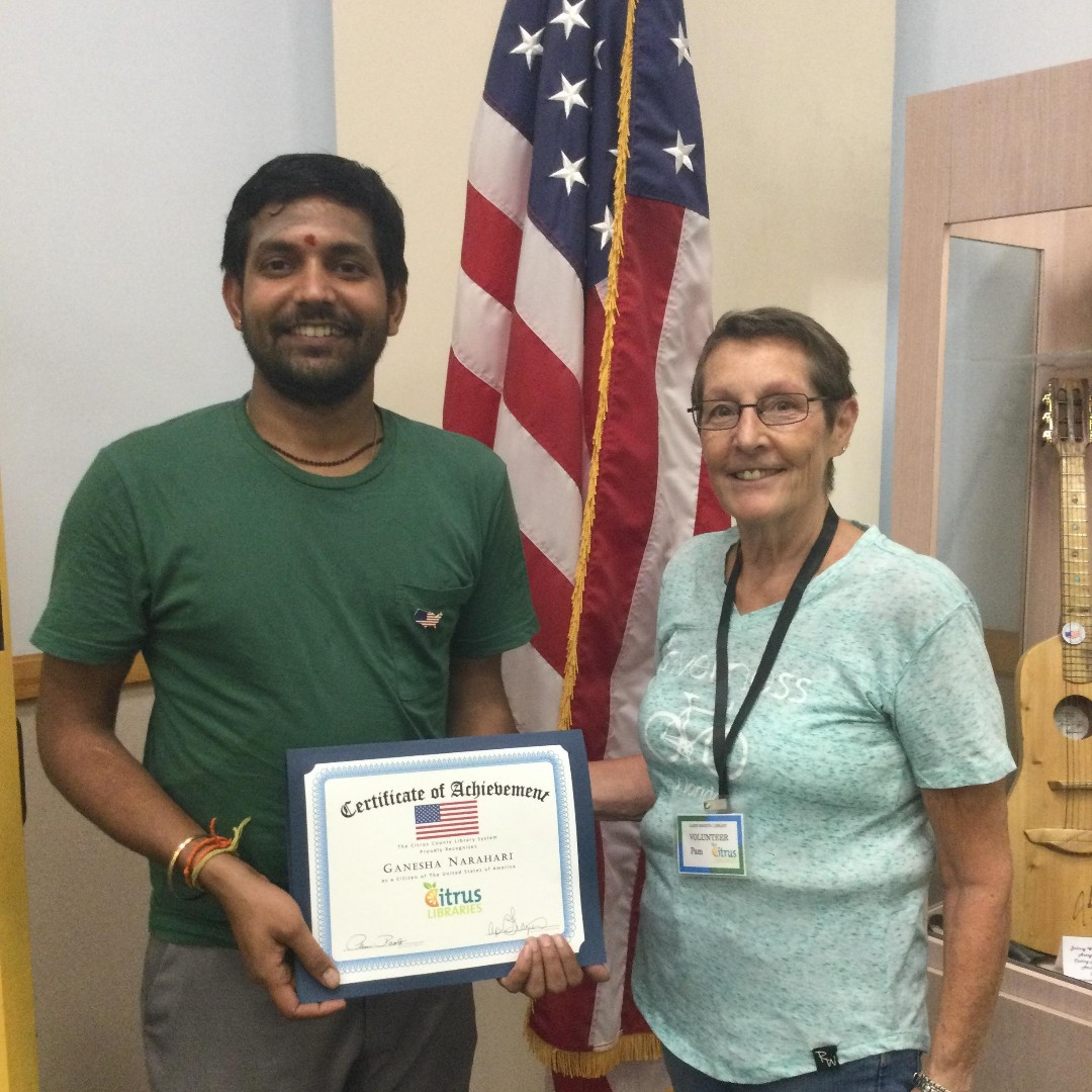 Adult Literacy Student Ganesha holding a certificate of achievement for passing the Naturalization exam with his Tutor Pam